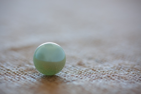 round marble displayed on rough textured background as abstract ball seperated from the soft background