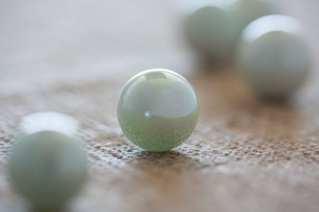 round marbles displayed on rough textured background as abstract Stock Photo