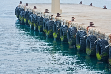 large tyres used on pierside warf to protect commerial boats when tied up in harbor Stock Photo