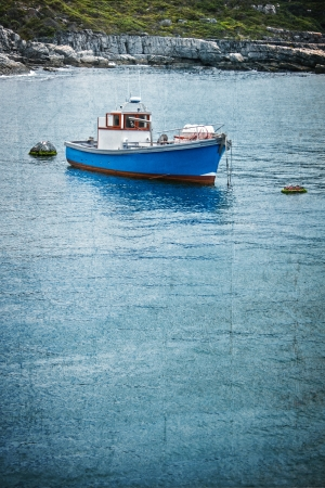 single boat at anchor in a bay with blue textured overlay Stock Photo
