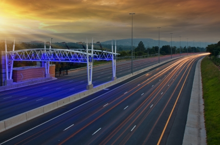 electronic toll gantry over a hiway of lights of moving vehicles Stock Photo