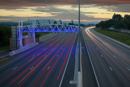 electronic toll gantry over a hiway of moving vehicles against a dusky sky Stock Photo