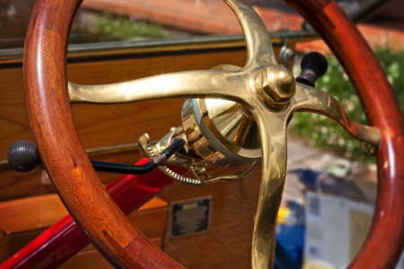 old vintage car steering wheel with wooden hand grip and brass centre