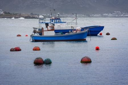 two commercial fishing boats at anchor in a gloomy bay