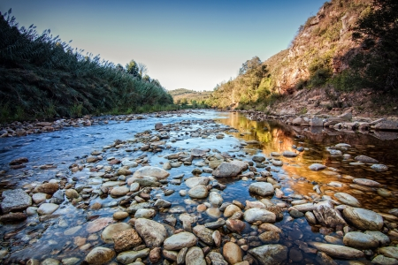rocky river creek in blue morning light with water and textured round stones Stock Photo