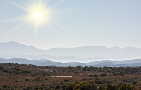 viewpoint of distant mountains with a bright sum shining in a clear sky Stock Photo