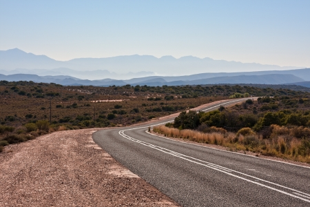 viewpoint of distant mountains with a country road receeding into the distance