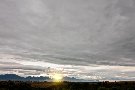 grey stormy cloudscape with a distant horizon and sunshine popping over mountains