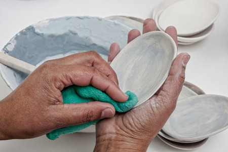working hands handling ceramic crockery applying color in preparation for glazing