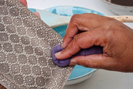 closeup detail of a textured hand applying colour to ceramic crockery