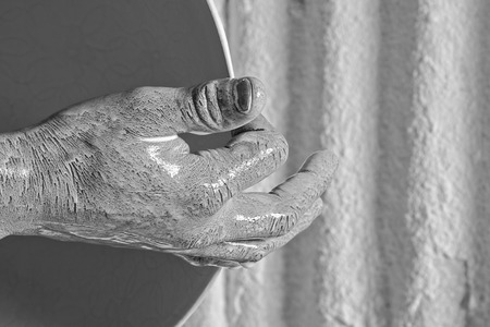 detail of a workers hand dripping with milky white liquid, holding a ceramic bowl