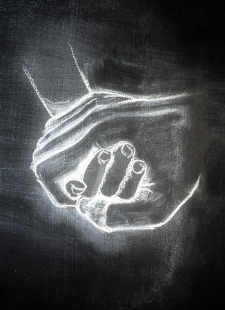 white chalk on a blackboard of nurturing hands holding and helping another