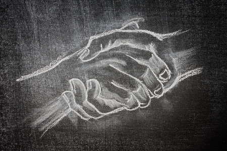 white chalk on a blackboard of a handshake illustration with two hands holding closing a deal or helping