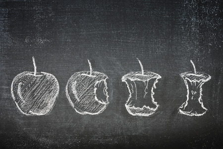 four stages of an apple being eaten till the core, chalk illustration on a blackboard