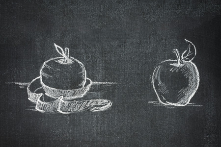 one whole and one peeled apple on a blackboard white chalk Stock Photo