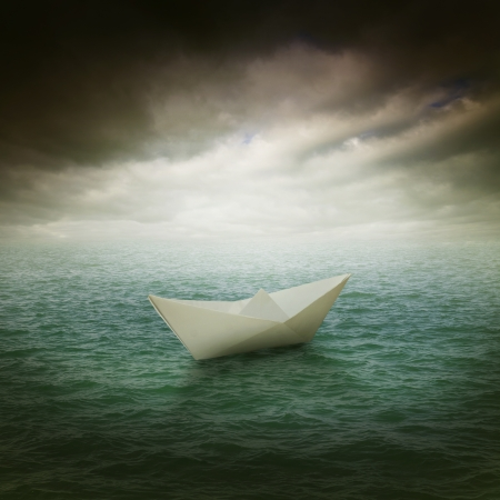 storm clouds: paper boat in the stormy ocean Stock Photo
