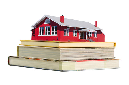 schoolhouse: Red brick old fashion schoolhouse on a stack of educational school books representing education.