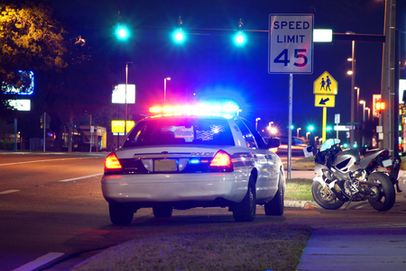 pulled over: Police car with its lights flashing has a motorcycle rider pulled over on the side of the road at night