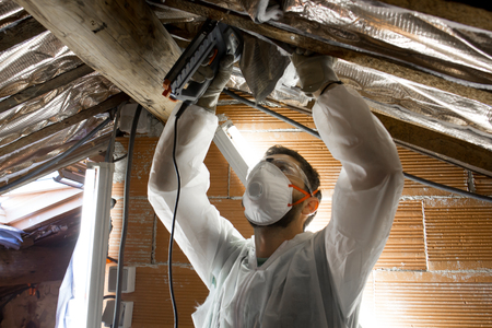 Man makes thermal insulation of the attic of the house
