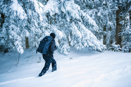 Man walks alone in the snow with forest in background - French Alps Stock Photo