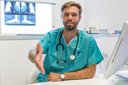 Young surgeon doctor reaches out to us Zdjęcie Seryjne