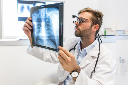 Serious attractive doctor examining an x-ray 写真素材