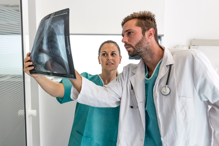 Doctor and nurse examining X-ray of patient in hospital 写真素材