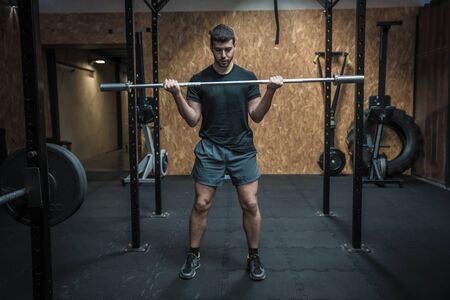Attractive man working out fitness and lifting heavy barbell