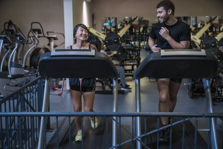 Attractive young people working out cardio on treadmill machine