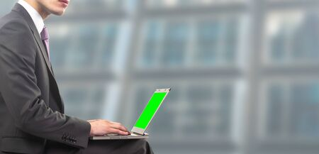 businessman sitting on laptop with green screen