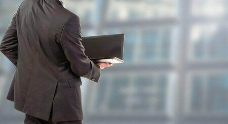 businessman standing back works on laptop 写真素材 - 134748758