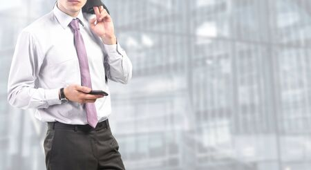 businessman standing relaxed holding smartphone 写真素材