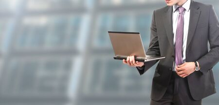 businessman standing works on laptop