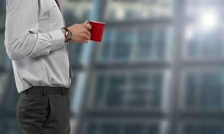 Businessman standing with red cup of coffee 写真素材