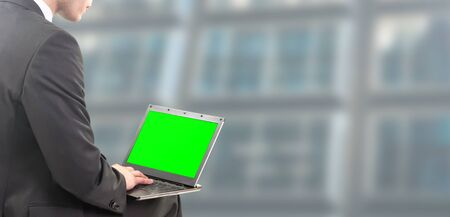 Businessman sitting in office with green screen