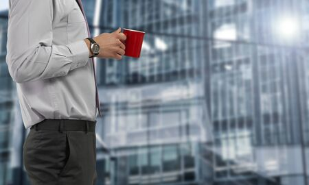 Businessman drinks in coffe red cup