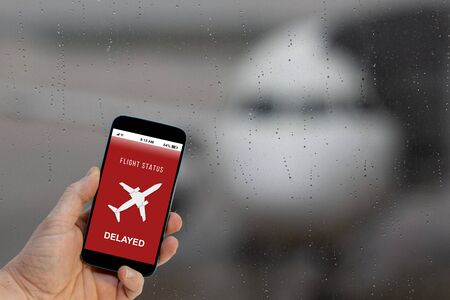Flight delayed notification on Smartphone application announces bad news to tourist 写真素材