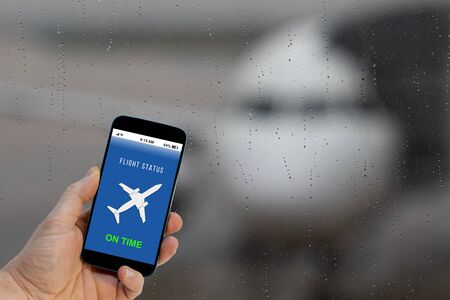 Flight on time notification on Smartphone application announces good news to tourist 写真素材 - 135818644