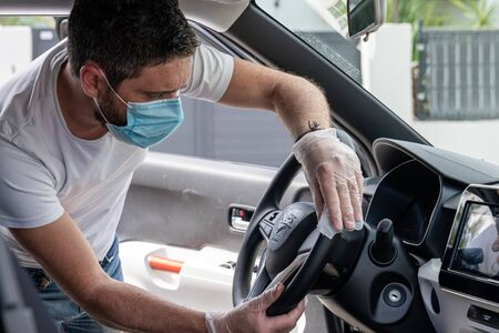 Covid-19, man with medical mask and gloves disinfects his car with a cleaning cloth Stock Photo - 149451812