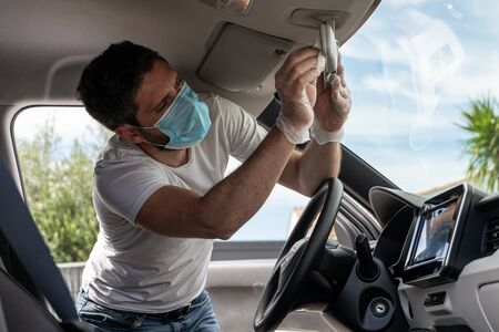 Covid-19, man with medical mask and gloves disinfects his car with a cleaning cloth Stock Photo - 149451814
