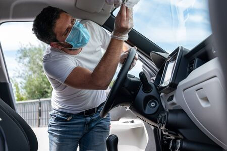 Covid-19, man with medical mask and gloves disinfects his car with a cleaning cloth Stock Photo - 149451827