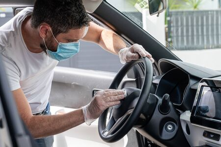 Covid-19, man with medical mask and gloves disinfects his car with a cleaning cloth