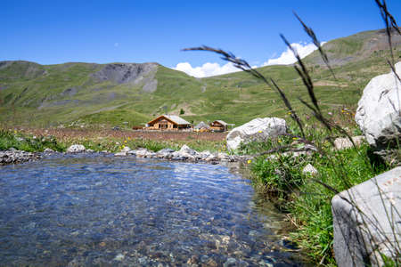 beautiful meadow with a little stream of water and a wooden chalet in background at summer