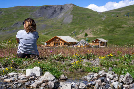 woman sitting in beautiful meadow with little stream of water in mountain