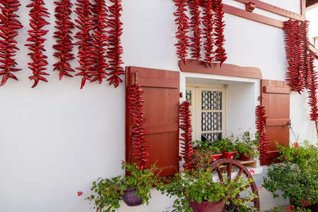 Ezpeleta, Red Espelette peppers drying in the wall of Basque house in Espelette village in France 写真素材