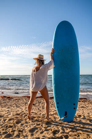 Beautiful surfer girl on the beach at sunset with a blue longboard
