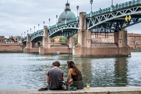 Couple sitting on the edge of the Garonne in Toulouse with the Saint-Pierre bridge in the background, France 写真素材