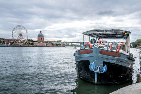 Tourist boat on edge of the Garonne river with Saint Pierre Bridge in background- Toulouse, France 写真素材