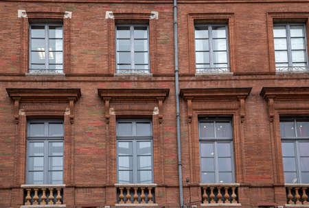 Facade of an old building with red brick in Toulouse the Pink city in France