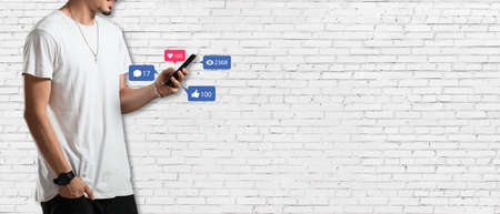 Social media concept - Banner with young man holding smartphone and with social media icon